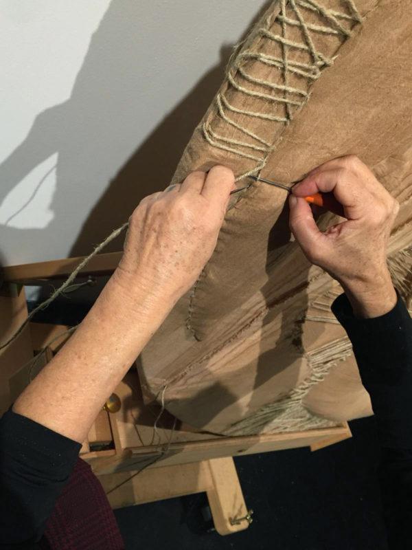"""Atelier#2 - 2018 MACRO Museo di Arte Contemporanea ROMA Diametro 150 cm Tela su telaio. Imbottitura in cotone. Cuciture, nodi e tiranti con corde varie. Nero - Atelier#2 Il Nero delle pareti dell'atelier è stato la mia grotta. La luce dei fari puntati sul cubo dai divisori di cristallo ha illuminato il processo creativo e di ricerca: il mio procedere. Come in una capsula spaziale ho iniziato il mio viaggio all'interno di quell'assoluto Nero. I visitatori, particelle di realtà, nuotandoci dentro silenziosamente, hanno partecipato a questo mio """" fare"""", alcuni con il desiderio di condividere il viaggio, altri di essere solo spettatori, altri ancora di essere testimoni degli occhi visionari di un artista. Niente avrebbe potuto interpretare meglio di questo Nero lo stato di concentrazione, ricerca, fatica e lotta per la realizzazione di un'Opera. A sottolineare la focalizzazione di questo """"fare"""", ho scelto di lavorare simbolicamente sulla forma del cerchio, come fosse l'occhio di un microscopio, per intraprendere il """"viaggio all'interno"""", il viaggiarsi dentro. """"Inside IV"""" fa parte della mia ricerca sull'Organico: andare oltre la Tela-Pelle, entrare nei tessuti, nei suoi reticolati e fibre, nelle linee dinamiche, nelle connessioni infinite tra cellula e cellula. E proprio per dare maggior risalto alle connessioni e ai loro tracciati, ho srotolato sul pavimento nero dell'atelier gomitoli di corda a collegare l'arazzo """"Inside II"""", già realizzato in precedenza, al Cubo-Artista: percorsi simbolici tra il finito e il suo divenire, tra il buio dell'indistinto e la luce della visione, tra l'opera e il suo autore."""